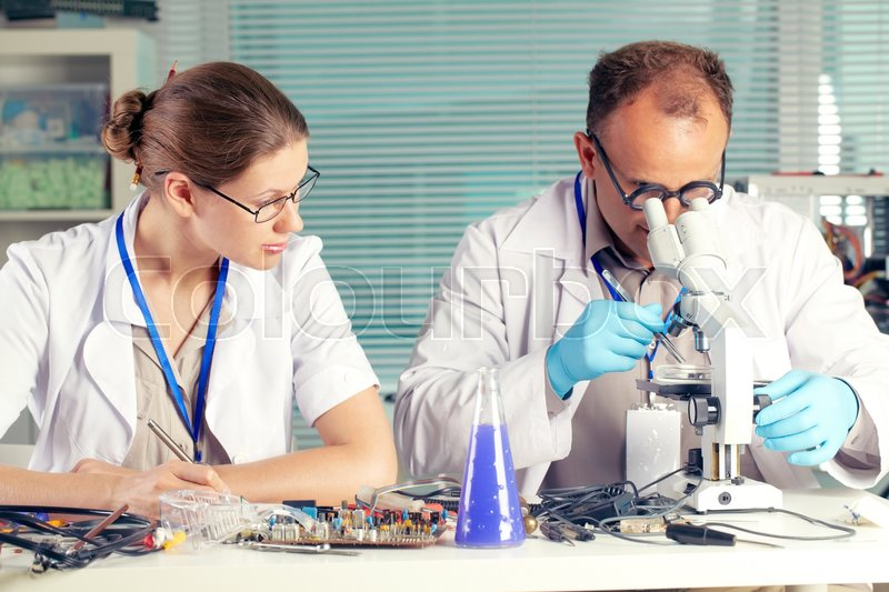 Stock image of 'Man examining something with microscope while woman writing results'