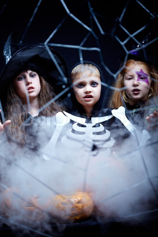 Stock image of 'Two girls dressed in witches conjuring and a boy dressed in skeleton appearing in the smoke'