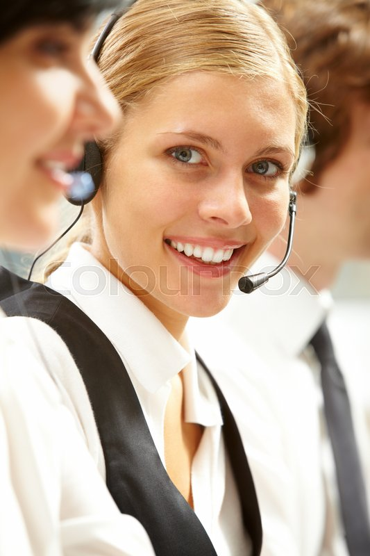 Stock image of 'A portrait of young businesswoman in headphones looking at camera and smiling among her colleagues'