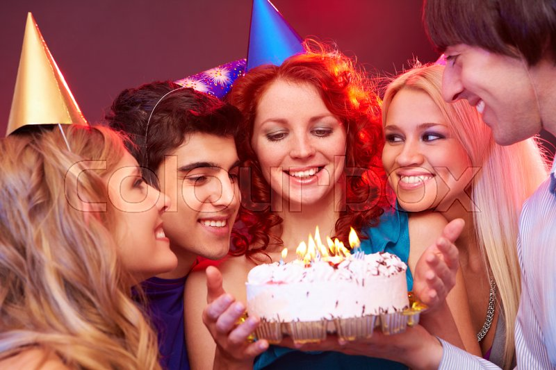 Stock image of 'Four young people congratulating their friend, presenting her a birthday cake, looking at her and the cake and smiling'