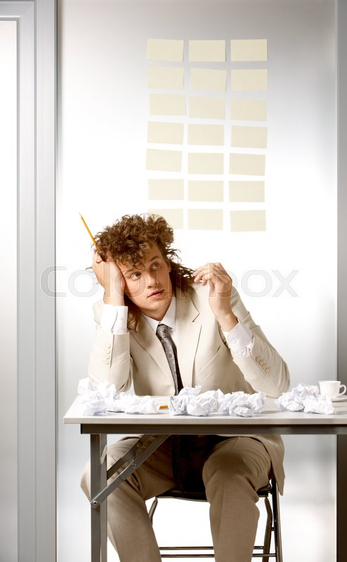 Stock image of 'Portrait of pensive boss sitting at the table in the office'