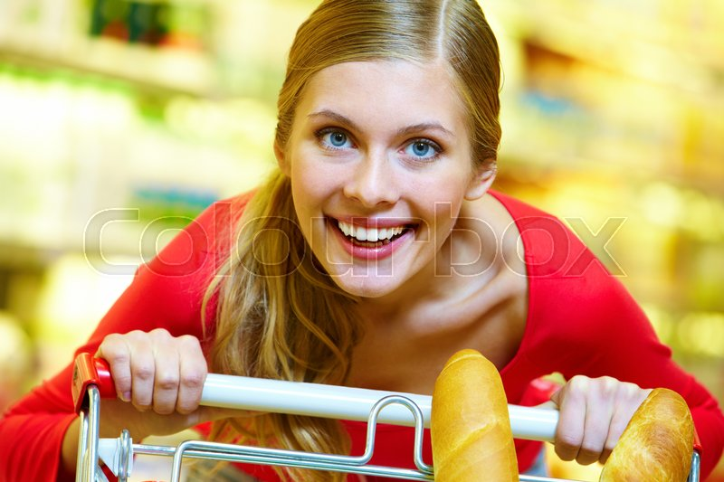 Stock image of 'A young woman pulling a trolley, looking at camera and smiling'
