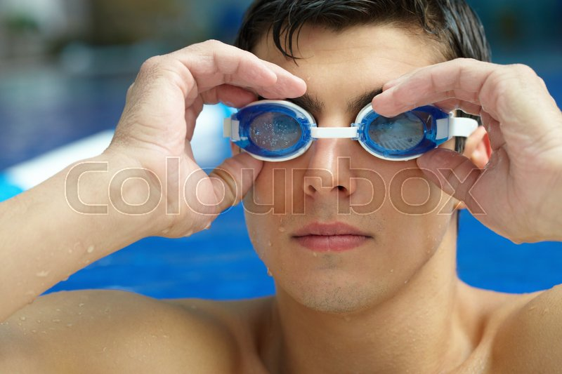 Stock image of 'Portrait of a swimmer putting on his goggles in the swimming pool'
