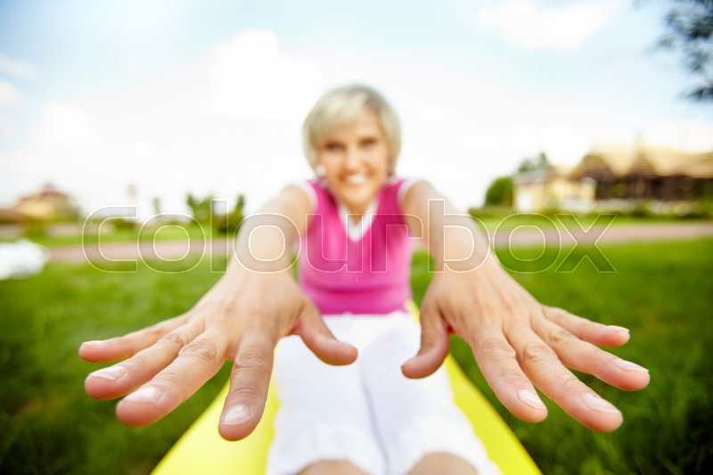 Stock image of 'Stretched image of a woman doing exercises with focus on her hands'