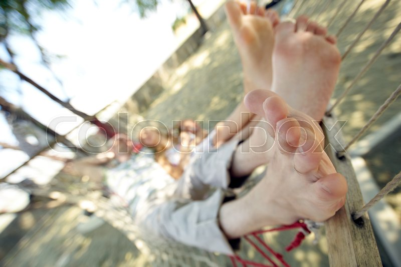Stock image of 'Feet of woman and man relaxing in hammock'