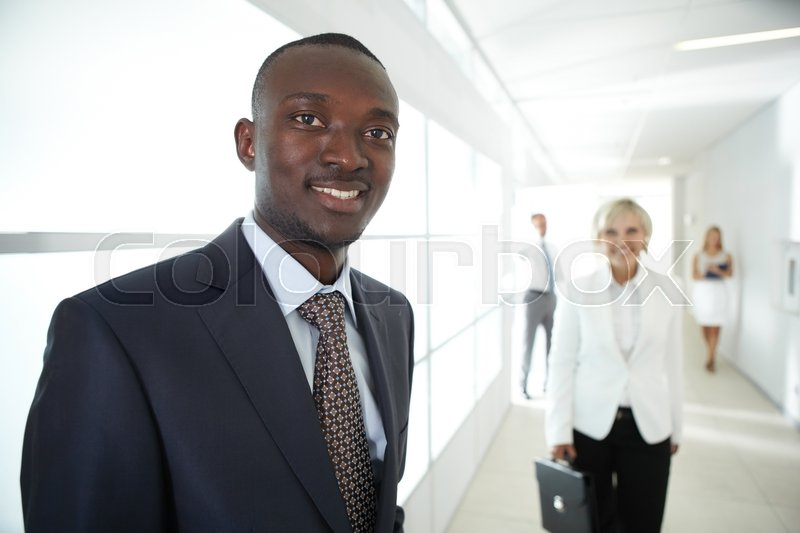 Stock image of 'Smiling businessman looking at camera with business people behind'