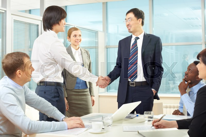 Stock image of 'Businessmen handshaking while business people sitting at the table'