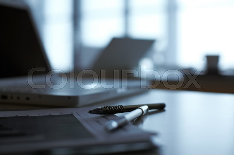 Stock image of 'A notebook and pens lying on table with laptop on background'