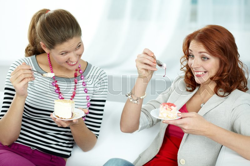 Stock image of 'Female friends eating pastries and having fun'