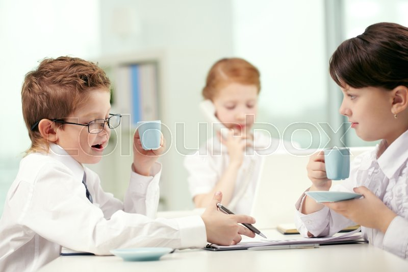 Stock image of 'Businesspeople-like children drinking coffee and discussing documents in office'