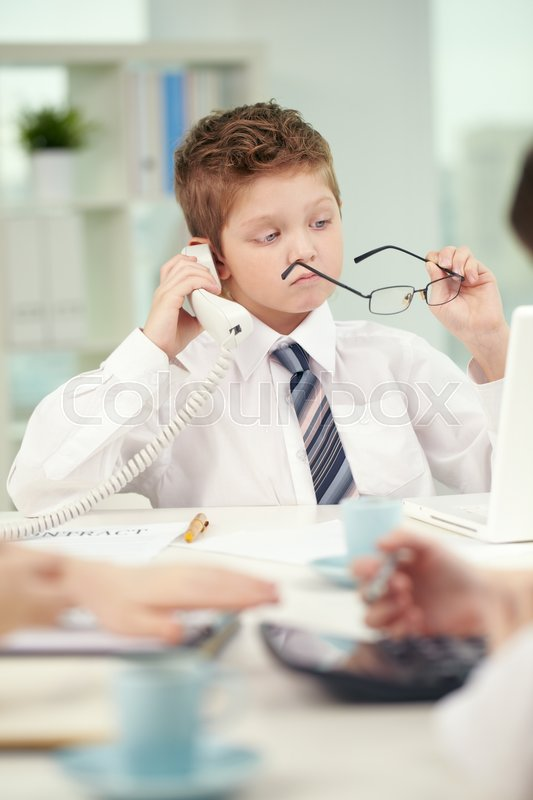 Stock image of 'Portrait of cute little boy talking on the phone and holding glasses in hand'