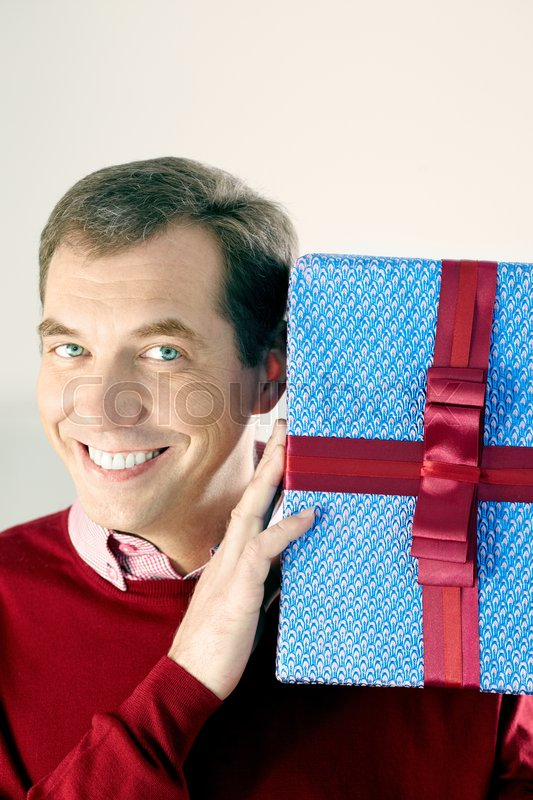 Stock image of 'Portrait of man holding a huge gift box and smiling'