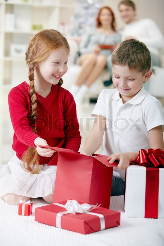Stock image of 'Little children unpacking gift boxes at home and examining its content'