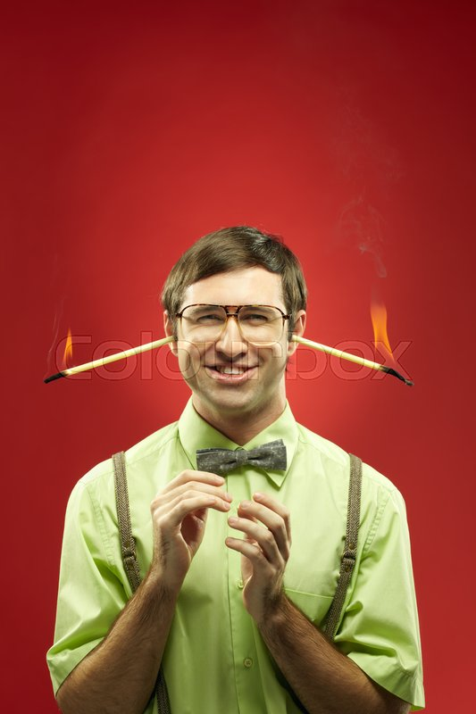 Stock image of 'Portrait of man in glasses with burning sticks in his ears having an idea'