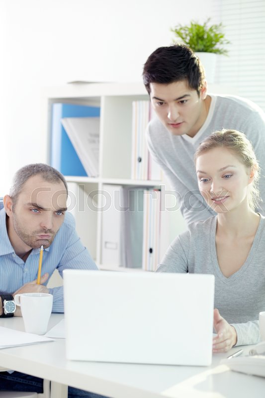 Stock image of 'Three business people concentrated on computer presentation'