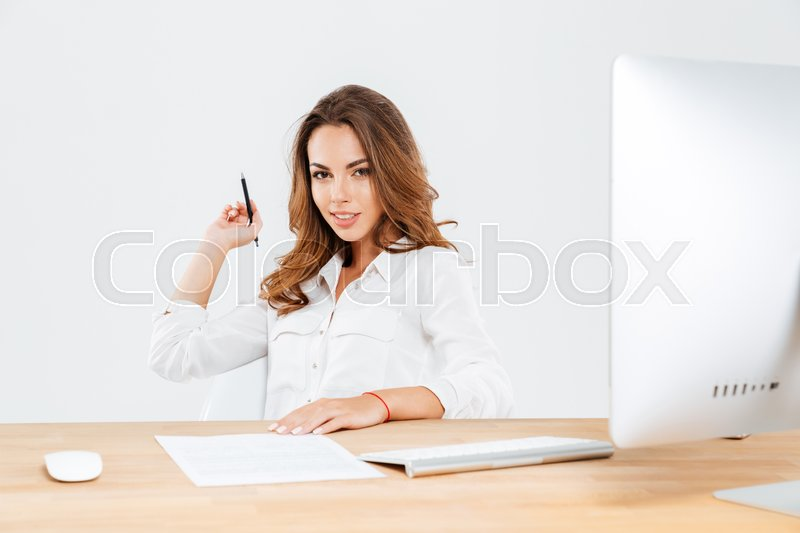 Stock image of 'Attractive young businesswoman holding pen while sitting at the office desk with laptop'