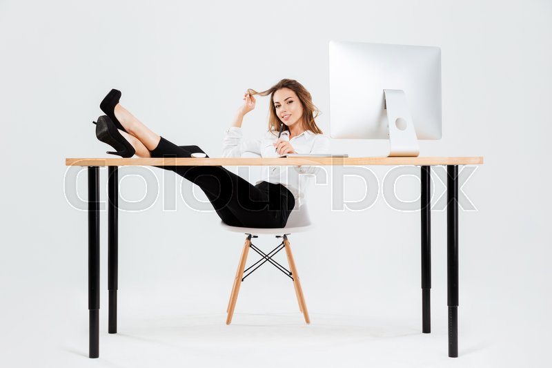 Stock image of 'Smiling young businesswoman using laptop and writing with legs on desk over white background'