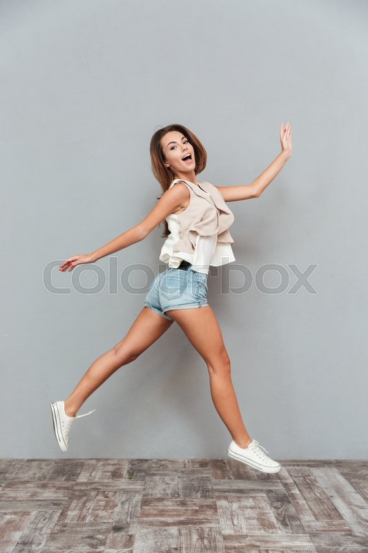 Stock image of 'Full length portrait of a smiling pretty woman jumping isolated on a gray background'
