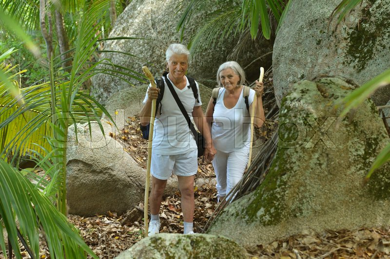Stock image of 'Beautiful happy elderly couple rest at tropical resort with backpacks'