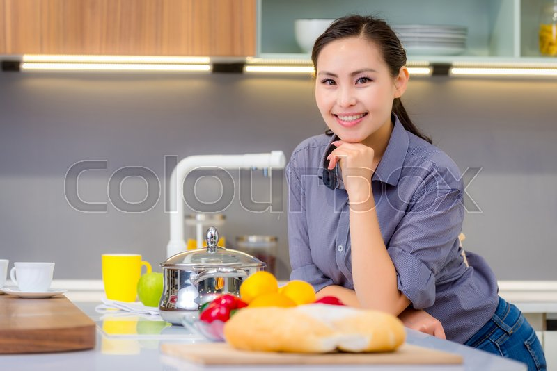 Stock image of 'Young beautiful happy asian woman in the kitchen'