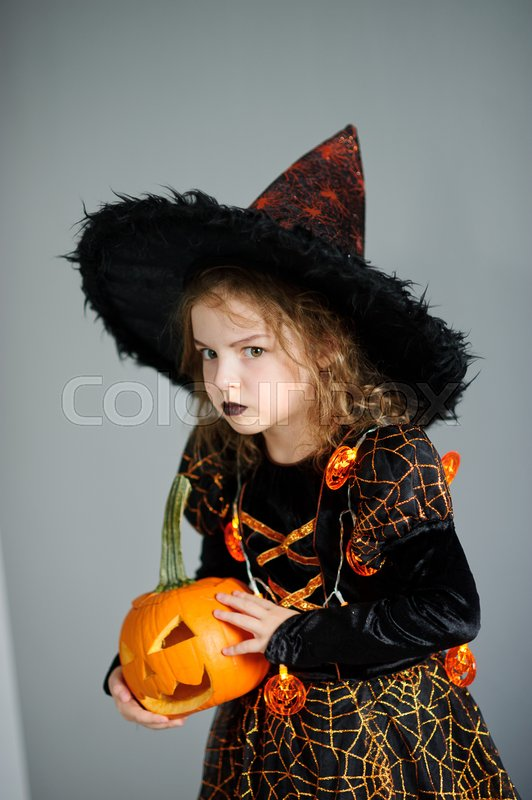 Stock image of 'Halloween. Girl portray evil sorceress.She is wearing black-and-orange dress and hat. From under his hat sticking disheveled hair. Girl has an evil expression. In hands at her pumpkin - Jack o lantern'