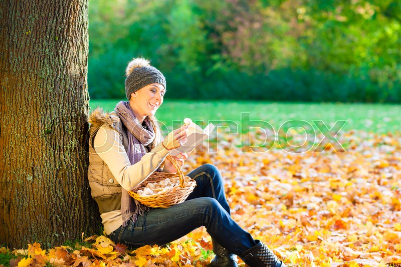 Stock image of 'Woman reading book on mushroom foray'
