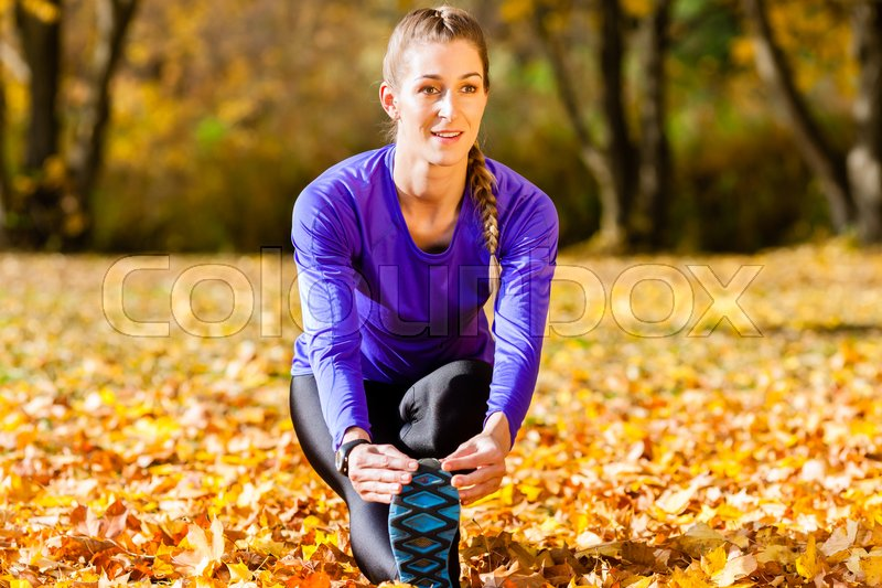 Stock image of 'Woman doing gymnastics in autumn foliage'