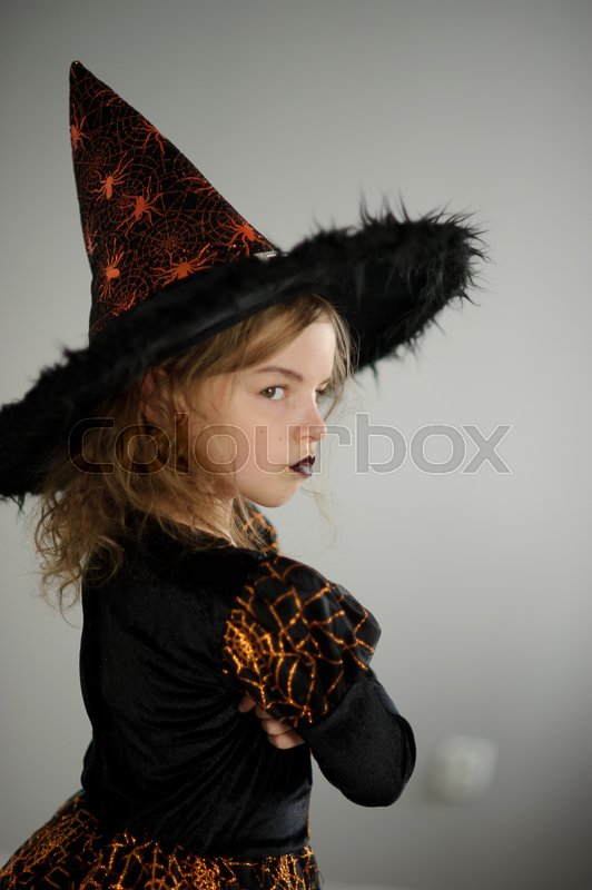 Stock image of 'Preparation for Halloween. Cute girl 8-9 years shows the evil fairy. She is dressed in black and orange dress and a big hat. The girl tries to make an evil look. Children adore Halloween'