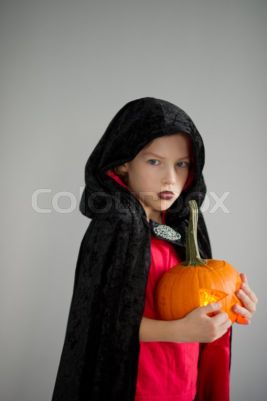 Stock image of 'All Hallows Eve. Boy age dressed in a costume for Halloween. He represents the evil wizard. Boy is gowned in a black-red toga with a hood. He holds pumpkin with a candle inside - Halloween symbol.'