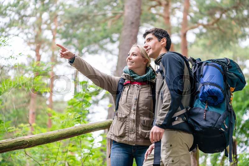 Stock image of 'Young couple, woman and man, on hike looking for the right trail on map'
