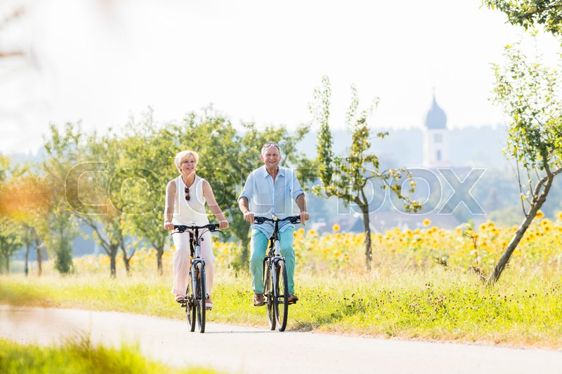 Stock image of 'Senior couple, woman and man, riding their bikes along field of sunflowers'