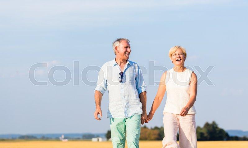 Senior woman and man holding hands having walk on field, stock photo