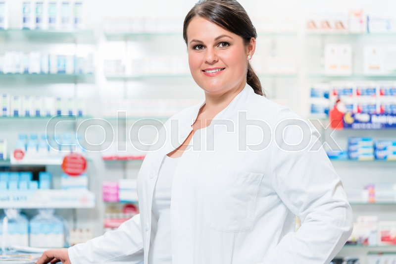 Stock image of 'Pharmacist in chemist shop in front of shelves with drugs looking at camera'