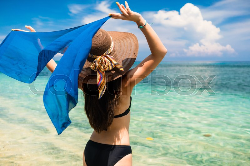 Stock image of 'Woman tourist with blue silky scarf at tropical beach on vacation'