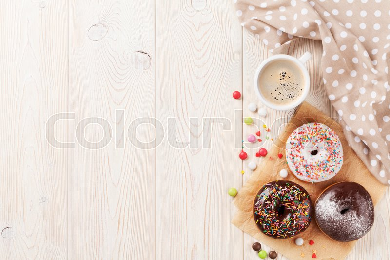 Stock image of 'Donuts and coffee on wooden table. Top view with copy space'