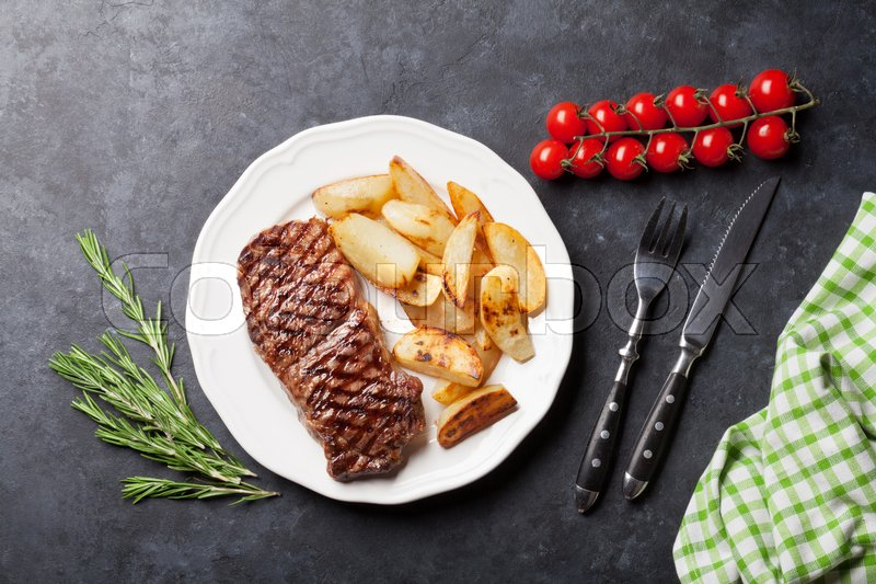Grilled striploin steak with roasted potato on plate over stone table. Top view, stock photo