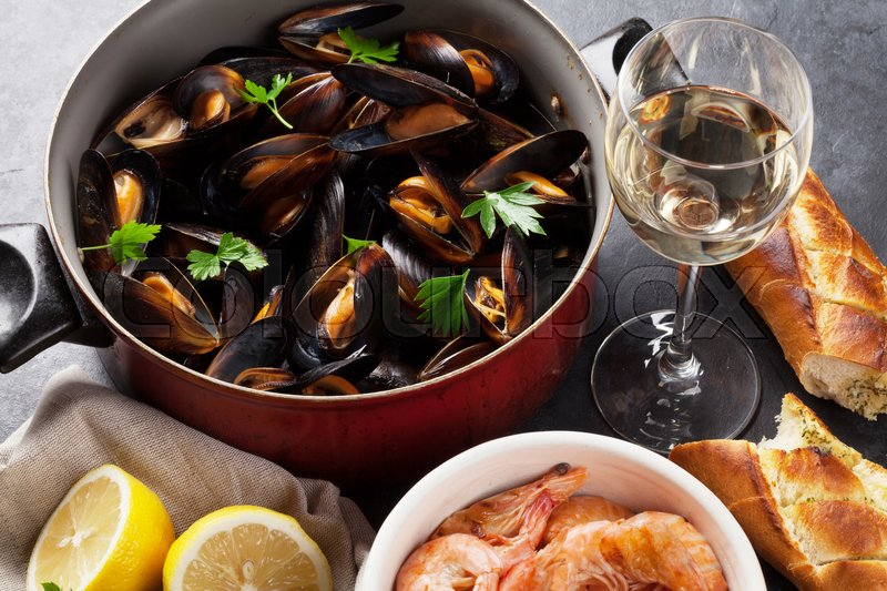 Stock image of 'Mussels, shrimps and white wine on stone table'