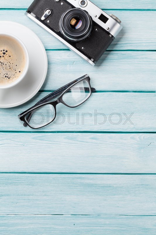 Stock image of 'Wooden table with camera, glasses and coffee. Top view with copy space. '