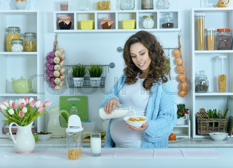Stock image of 'beautiful pregnant woman with  milk at kitchen'