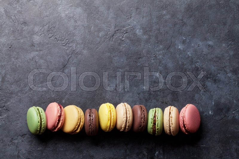 Stock image of 'Colorful macaroons on stone table. Sweet macarons. Top view with copy space for your text'