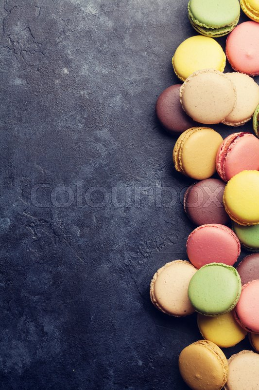 Stock image of 'Colorful macaroons on stone table. Sweet macarons. Top view with copy space for your text. Retro toned'