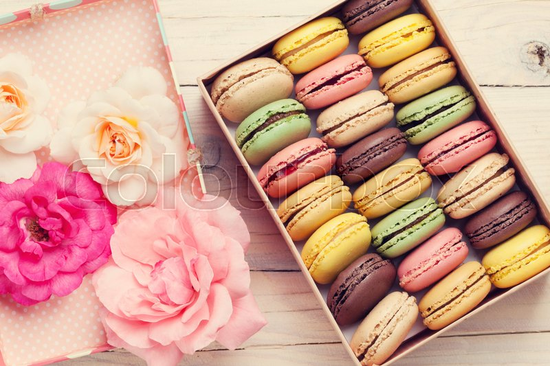 Stock image of 'Colorful macaroons and rose flowers on wooden table. Sweet macarons in gift box. Top view. Retro toned'