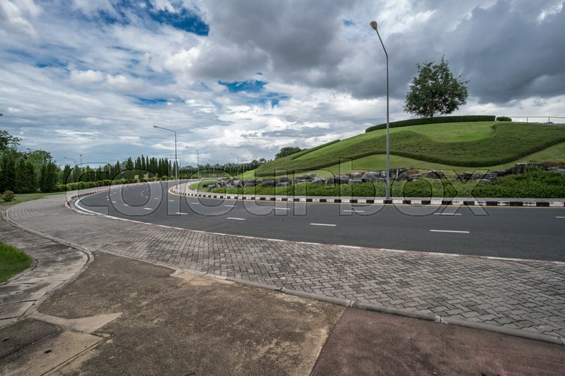 Stock image of 'Asphalt road round Garden small hill with cloud and sky'