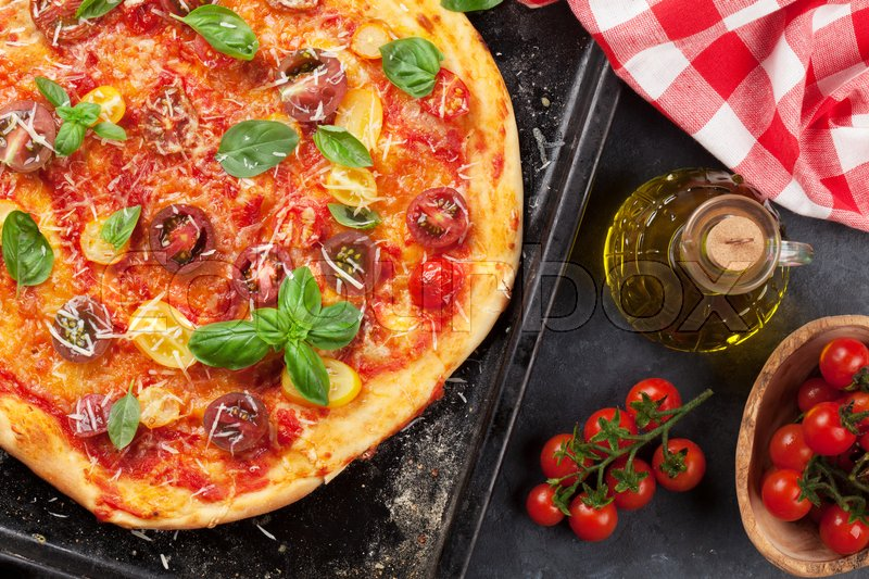 Stock image of 'Homemade pizza with tomatoes, mozzarella and basil on dark stone table'