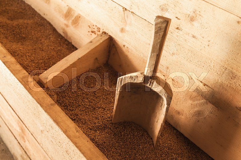 Stock image of 'Old wooden scoop in a box of grain, vintage windmill equipment'
