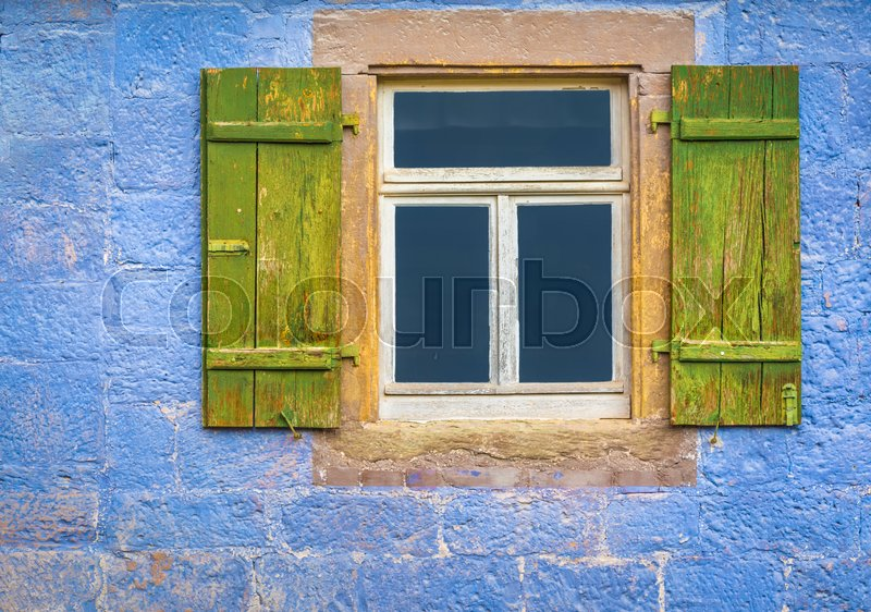 Stock image of 'Architectural details over a window with wooden shutters, from an antique german house with walls painted in blue.'