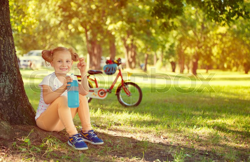 Stock image of 'Cute little child girl sit under the tree with bottle in her hands. Bicycle on background'