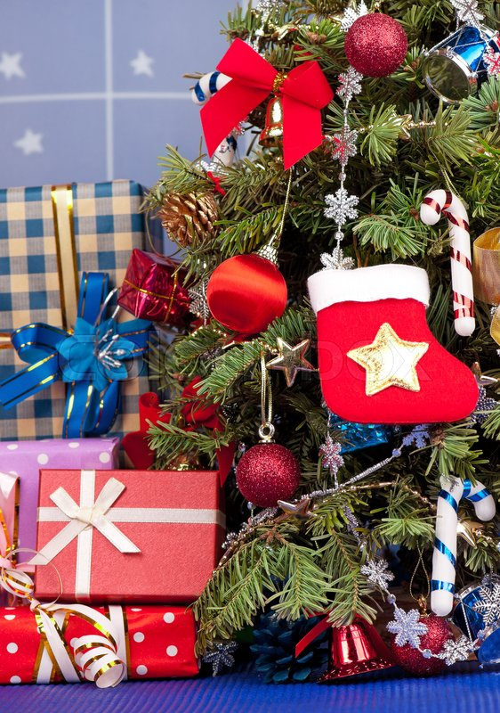 Stock image of 'Christmas toy balls with garland over presents and christmas spruce background'