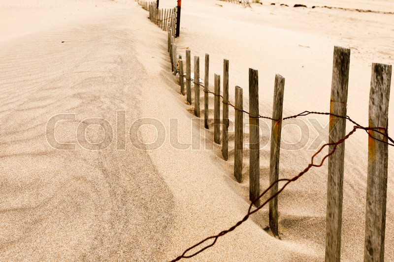 Stock image of 'Wooden fence, grass and white sand dunes on the beach.'