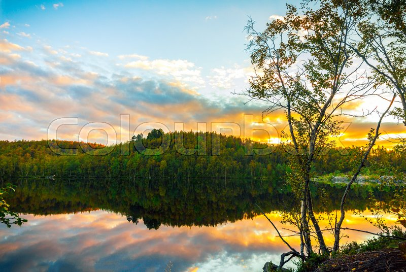 Stock image of 'Bright sunset on forest lake in autumn'